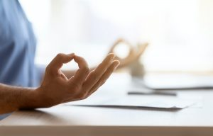 Zen. Closeup shot of unrecognizable man meditating while working in office